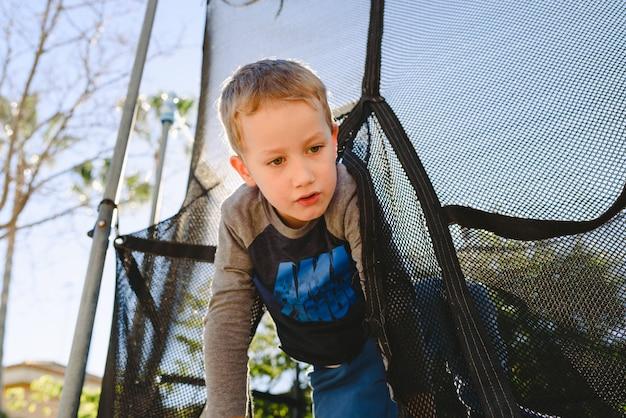 Dziecko zabawy na wiosnę na trampolinie o zachodzie słońca.