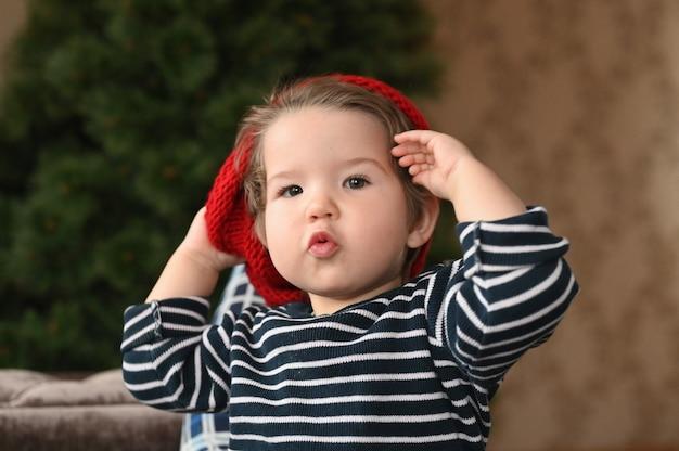 Dziecko zakłada kapelusz. czerwony kapelusz i dziecko. pokazuje palec. dziecko ma 0-1 lat. roczny portret dziecka.