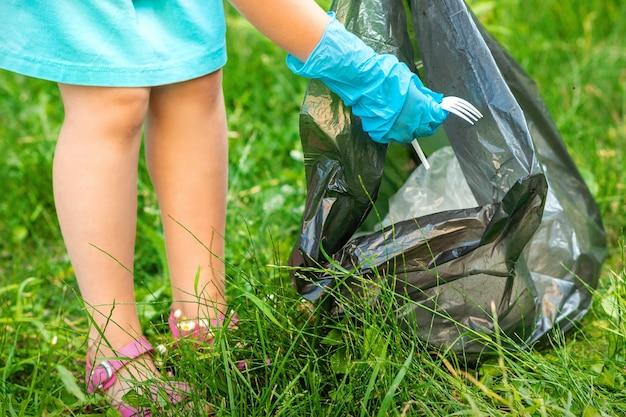 Dziecko zbiera plastikowe śmieci z trawy wyrzucając śmieci do worka na śmieci w parku