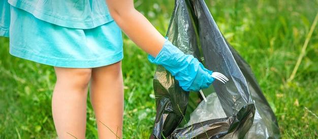 Dziecko zbiera plastikowe śmieci z trawy