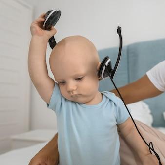 Dziecko ze słuchawkami taty w domu podczas kwarantanny
