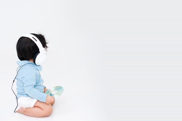 Dziecko ze słuchawkami w białym pokoju dobrze się bawi.