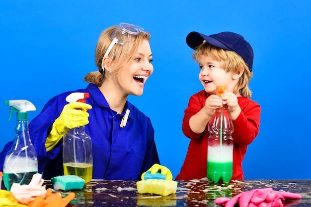 Dziecko ze śmiejącą się twarzą trzyma spray na stole dziecko siedzi przy drewnianym stole ze środkami czyszczącymi