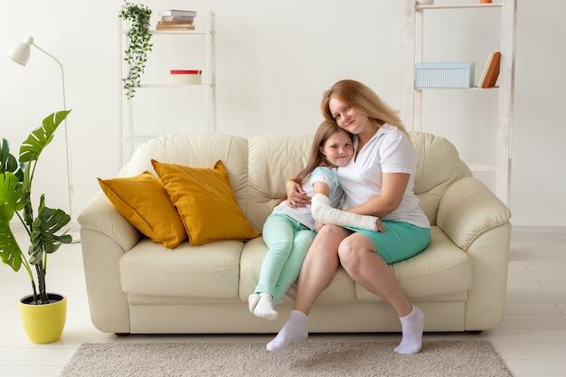 Dziecko ze złamaną ręką i gipsem spędza czas w domu z matką. choroby wieku dziecięcego, pozytywne
