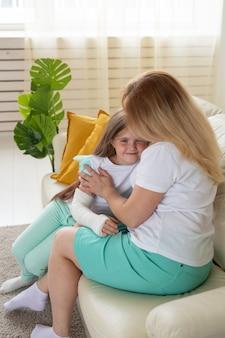 Dziecko ze złamaną ręką i gipsem spędza czas w domu z matką. choroby wieku dziecięcego