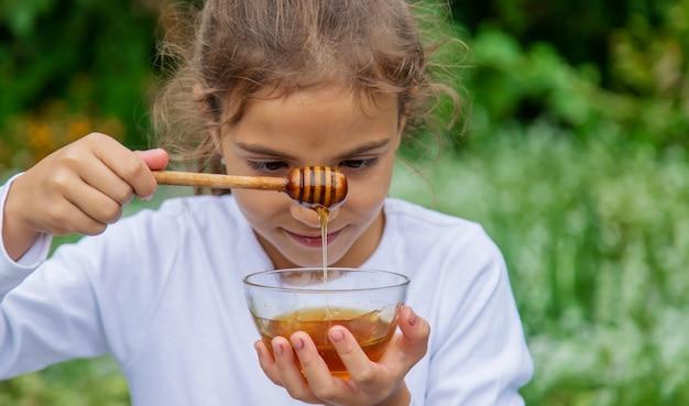 Dziecko zjada miód i jabłka. selektywne skupienie.