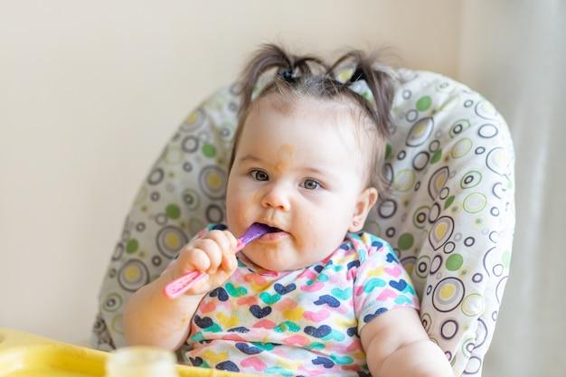 Dziecko zjada się łyżką tłuczonych ziemniaków ze słoika, koncepcja żywności dla niemowląt