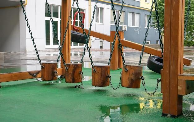 Dziedziniec wieżowców z nowoczesnym i dużym placem zabaw z drewna i plastiku w deszczowy letni dzień bez ludzi. pusty plac zabaw na świeżym powietrzu. miejsce do zabaw i sportów dla dzieci.
