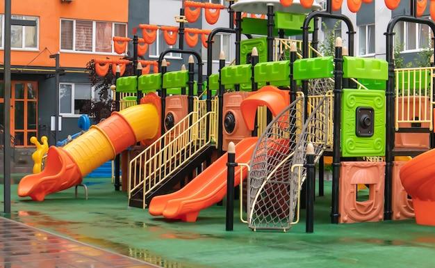 Dziedziniec wieżowców z nowym nowoczesnym kolorowym i dużym placem zabaw w deszczowy letni dzień bez ludzi. pusty plac zabaw na świeżym powietrzu. miejsce do zabaw i sportów dla dzieci.