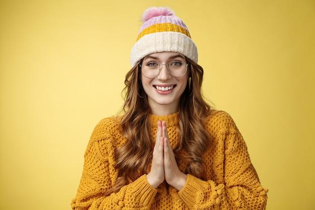 Dziękuje bardzo. portret uroczy przetargu śliczna europejska młoda kobieta na szczęście patrząc kamera kłaniając się uprzejmy pokaz namaste uznanie gest naciśnij dłonie razem uśmiechnięte żółte tło