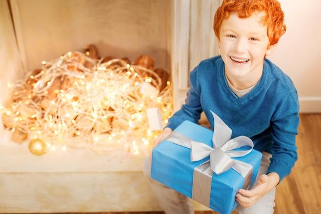 Dziękuję bardzo. widok z góry na emocjonalnego dzieciaka, który uśmiecha się, trzymając prezent gwiazdkowy i podekscytowany.