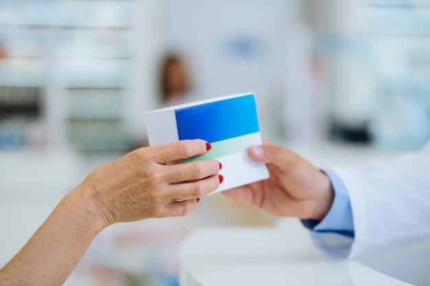 Dziękuję ci. profesjonalny farmaceuta konsultujący się ze swoim klientem i dający pudełko z niezbędnymi tabletkami