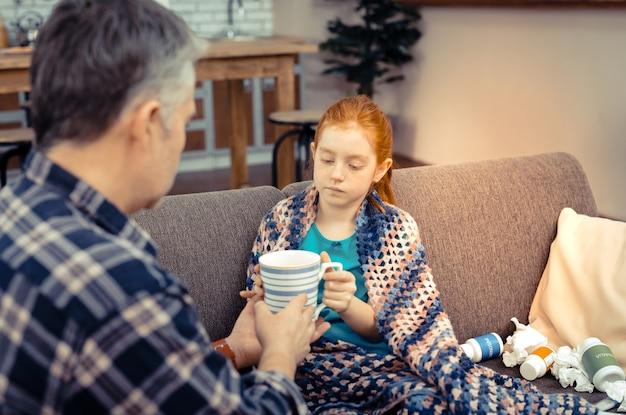 Dziękuję ci. przyjemna chora dziewczyna biorąca filiżankę herbaty z rąk ojca siedząc na kanapie