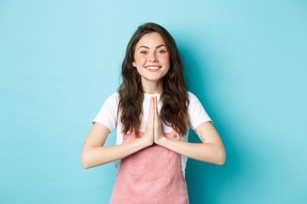 Dziękuję ci. uśmiechnięta śliczna dziewczyna pokazująca namaste, gest wdzięczności, prosząca o pomoc lub przysługę, uśmiechnięta zadowolona, dziękująca za przysługę, stojąca na niebieskim tle.