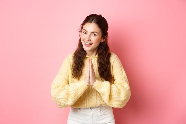 Dziękuję ci. uśmiechnięta uprzejma dziewczyna wita cię gestem namaste, kłaniając się i wyglądając przyjaźnie, wyraża wdzięczność, jest wdzięczna, stoi nad różową ścianą.