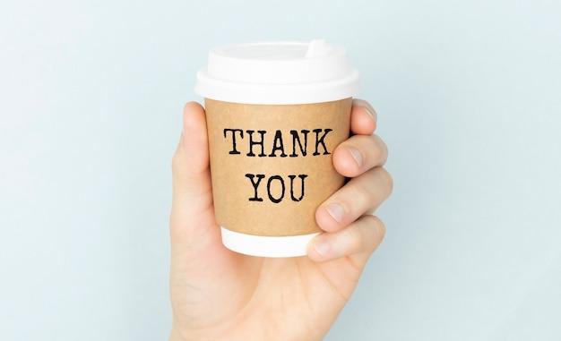 Dziękuję lub dziękuję koncepcji z filiżanką kawy w ręce na jasnym tle.
