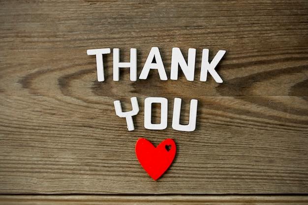 Dziękuję słowo - na białym tle tekst wdzięczności z czerwonym sercem.