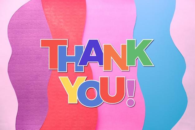 Dziękuje tekst w tęczowych literach na warstwowym kolorowym abstrakta papieru tle. dziękujemy lekarzom, pielęgniarkom, zespołom medycznym i kluczowym pracownikom dbającym o nasze życie podczas pandemii covid-19!