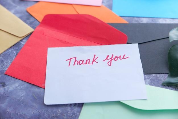 Dziękuję wiadomość i koperta na drewnianym stole