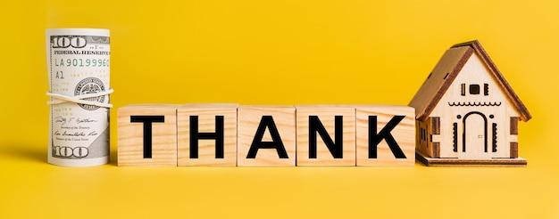 Dziękuję z miniaturowym modelem domu i pieniędzmi na żółtym tle. pojęcie biznesu, finansów, kredytu, podatków, nieruchomości, domu, mieszkania