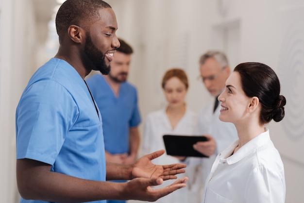 Dzielenie się ciekawymi doświadczeniami. przyjaźni, szczęśliwi zaangażowani lekarze, którzy spędzają przerwę na kawę w szpitalu i wyrażają zainteresowanie, dzieląc się pomysłami