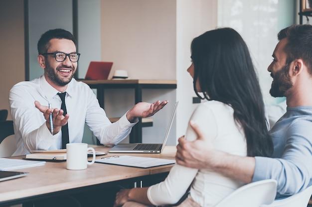 Dzielenie się dobrą wiadomością. szczęśliwa młoda para łącząca się ze sobą i słuchająca wesołego dojrzałego mężczyzny siedzącego przy biurku przed nimi i gestykulującego