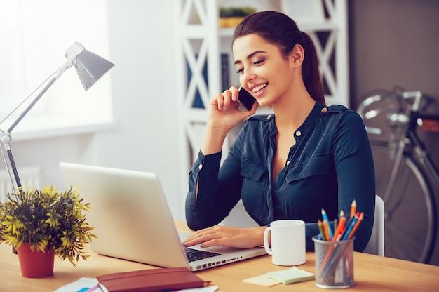 Dzielenie się dobrymi wiadomościami biznesowymi. atrakcyjna młoda kobieta rozmawia przez telefon komórkowy i uśmiecha się