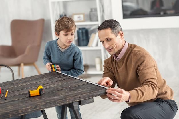 Dzielenie się doświadczeniem. atrakcyjny ciekawy mały jasnowłosy chłopiec trzyma miarkę i mierzy stół, a jego tata pomaga pomóc
