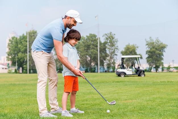 Dzielenie się doświadczeniem golfowym. wesoły młody człowiek uczy syna grać w golfa, stojąc na polu golfowym