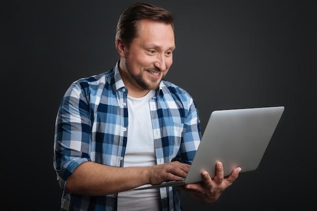 Dzielenie się ekscytującymi wiadomościami. koncentruje się dobrze wyglądający miły mężczyzna wpisując list, trzymając komputer i stojąc na białym tle na szarym tle