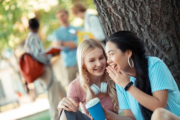 Dzielenie się opiniami. dwie uśmiechnięte plotkarki szepczące i rozmawiające o swoich przyjaciołach siedzących blisko siebie pod wielkim drzewem.