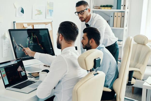 Dzielenie się opiniami. grupa młodych, nowoczesnych mężczyzn w strojach formalnych, pracujących przy komputerach, siedząc w biurze