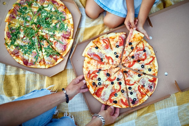 Dzielenie się pizzą, ręce wyciągające kawałek pizzy z pudełka na świeżym powietrzu, piknik rodzinny, jedzenie pizzy na obiad, dostawa fast foodów.