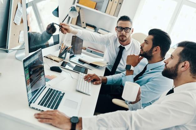 Dzielenie się pomysłami. grupa młodych, nowoczesnych mężczyzn w strojach formalnych, pracujących przy komputerach, siedząc w biurze