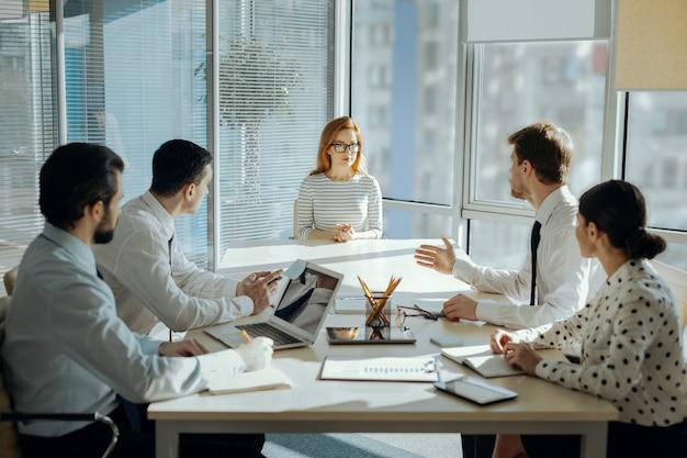 Dzielenie się pomysłami. sympatyczni, pracowici młodzi pracownicy siedzą przy stole ze swoją szefową i omawiają z nią wspólny plan projektu