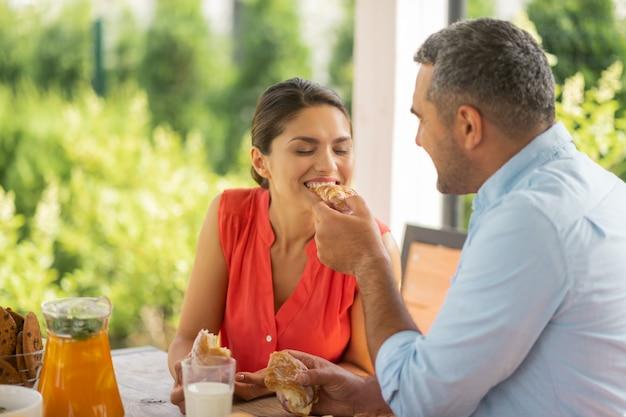 Dzielenie się rogalikiem. troskliwy mąż dzielący się rogalikiem z żoną podczas wspólnego śniadania