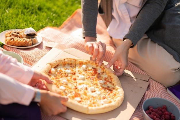 Dzielenie się serową pizzą. zbliżenie dwóch uczniów dzielących się pizzą z serem podczas lunchu na zewnątrz?