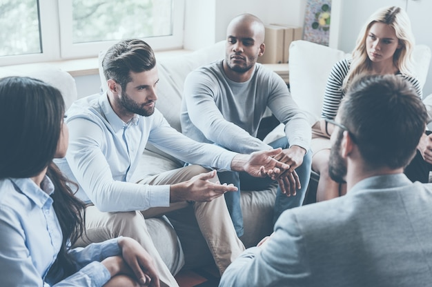 Dzielenie się swoimi problemami z grupą. grupa młodych ludzi siedzących w kręgu, podczas gdy jeden mężczyzna mówi coś i gestykuluje