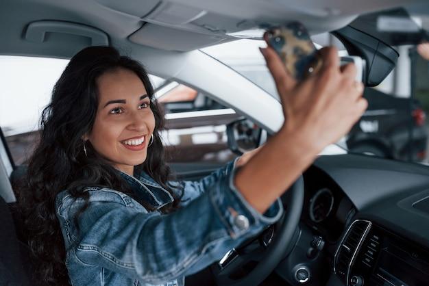 Dzielenie się szczęściem. śliczna dziewczyna z czarnymi włosami próbuje swojego nowego drogiego samochodu w salonie samochodowym