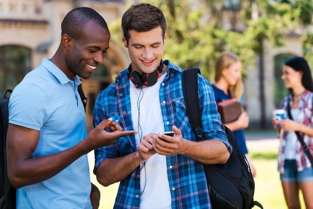 Dzielenie się wiadomościami z przyjaciółmi. dwóch wesołych mężczyzn patrzących na telefon komórkowy i uśmiechających się, a dwie kobiety rozmawiające w tle