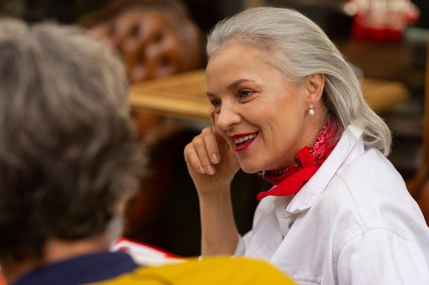 Dzielenie się wrażeniami. piękna dorosła kobieta siedzi z mężem przy stoliku kawiarnianym, opowiadając mu historię.