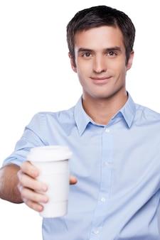 Dzielimy się z tobą kawą. przystojny młody mężczyzna w niebieskiej koszuli trzyma filiżankę kawy wyciągniętą i uśmiechniętą, stojąc na białym tle