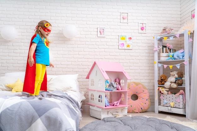 Dzielna śliczna dziewczynka chce wyskoczyć z łóżka, wyobrażając sobie lot.
