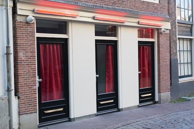 Dzielnica czerwonych latarni w amsterdamie. okna i drzwi, w których pracują prostytutki