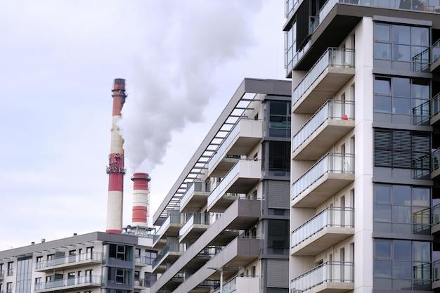 Dzielnica mieszkalna z dwiema fabrycznymi rurami przemysłowymi. zanieczyszczenia, ekologia koncepcja.