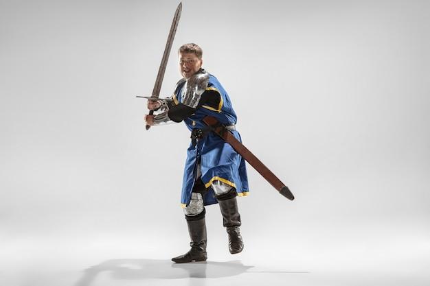 Dzielny rycerz w zbroi z profesjonalną bronią walki na białym tle na tle białego studia.