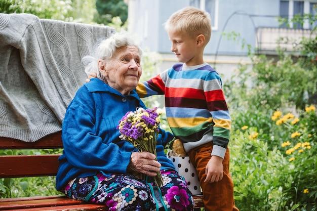 Dzień babci i dziadka zjednoczona rodzina razem starsza stara babcia przytula wnuka na zewnątrz wnuk