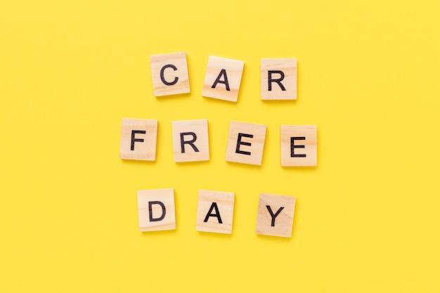 Dzień bez samochodu na drewnianych kostkach na żółtym tle