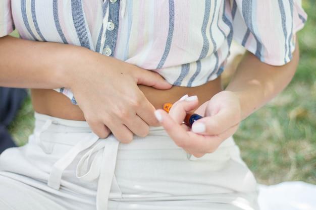 Dzień cukrzycy osoba wstrzykuje insulinę w brzuch w parku na świeżym powietrzu z powodu tej choroby