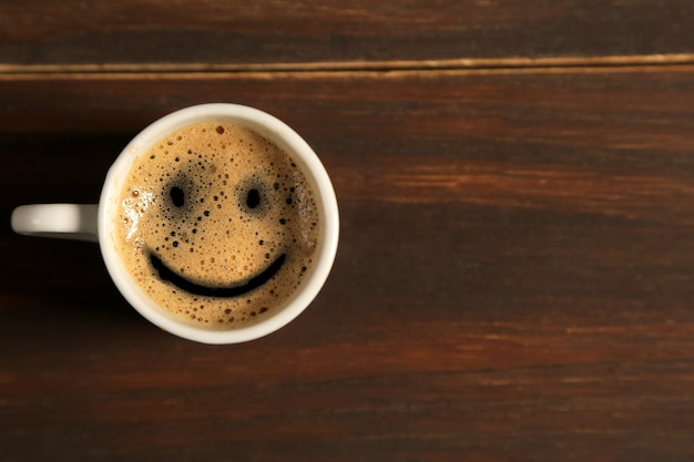 Dzień dobry filiżanka kawy uśmiech na drewnianym stole